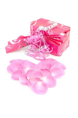 beautiful wrapped gift with rose leaves in heart shape over white background Stock Photo - 6304467