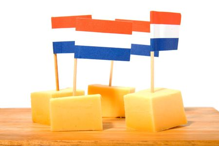cheese cubes on wooden board with Dutch flags for party over white background photo