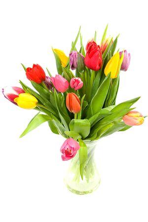 Kleurrijke Nederlandse tulpen in glazen vaas op witte achtergrond  Stockfoto