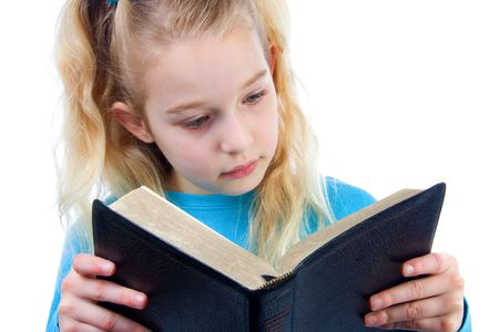 little blonde girl is reading the Holy Bible over white background Stock Photo