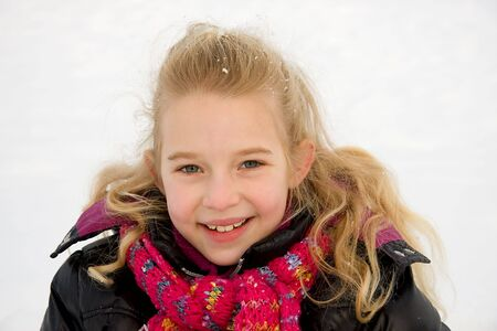 portrait of young blonde girl looking in camera and smiling. It is winter with snow Stock Photo - 6450791