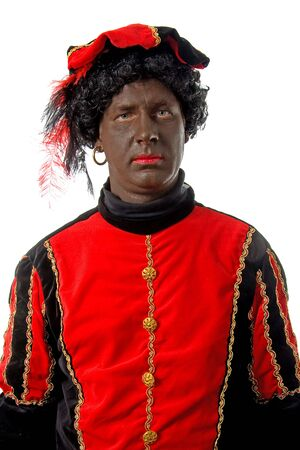 saint nicolaas: Zwarte piet ( black pete) typical Dutch character part of a traditional event celebrating the birthday of  Sinterklaas in december over white background looking into camera Stock Photo