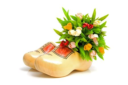 klompen: pair of traditional Dutch yellow wooden shoes with little tulips over white background
