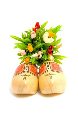 pair of traditional Dutch yellow wooden shoes with little tulips over white background Stock Photo - 6616270