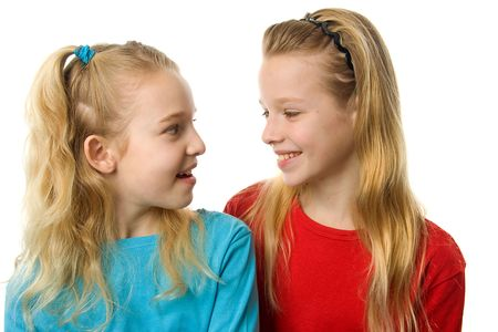 Two young blonde girl are laughing at each other, over white background Stock Photo - 6607390