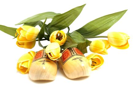 Typical Dutch wooden shoes with silk yellow tulips over white background Stock Photo - 6756772