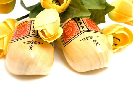 klompen: Typical Dutch wooden shoes with silk yellow tulips over white background Stock Photo
