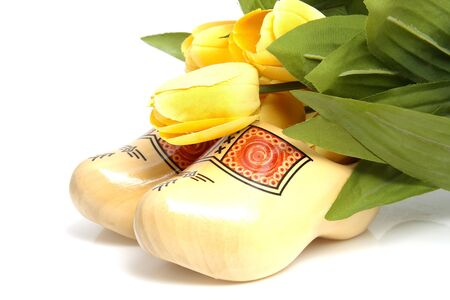 Typical Dutch wooden shoes with silk yellow tulips over white background Stock Photo - 6756678