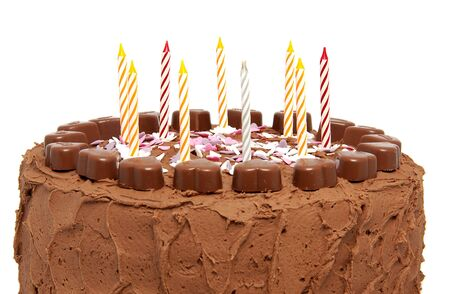 Chocolate birthday cake with candles over white background photo