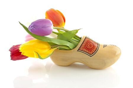 klompen: traditional yellow wooden shoe with colorful tulips isolated on white background Stock Photo