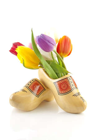 klompen: Pair of traditional yellow wooden shoes with colorful tulips isolated on white background