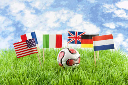 Flags and ball on soccer field over cloudy blue sky photo