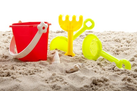colorful plastic toys for the beach on sand over white background photo