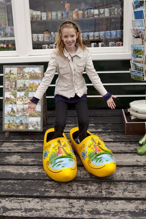 klompen: Girl with big typical wooden shoes before souvenis shop in Marken, the netherlands