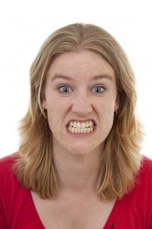 angry woman: Woman looks very angry in closeup over white background Stock Photo