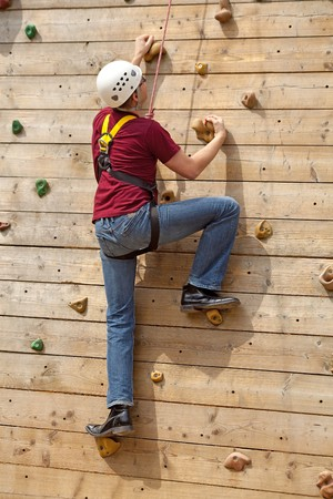 man is on climbing wall in the nature photo