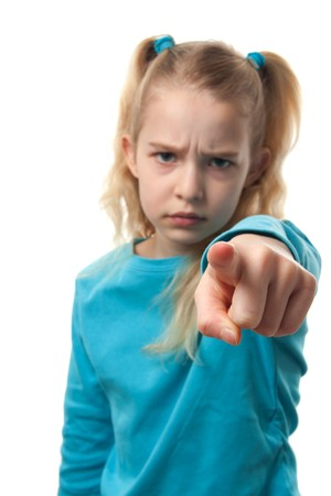 Young blonde girl is angry and pointing at you with focus on fingers an blur on face, over white background