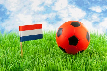 Orange ball and Dutch flag on soccer field against paper blue cloudy sky  photo