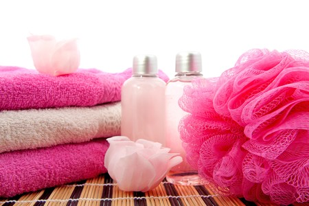 pink spa bathroom accessory on cane mat over white background photo