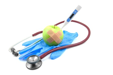 Health care: blue surgical glove, stethoscope and apple with thermometer over white background photo