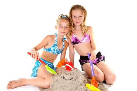 two Young blonde girls in beach wear playing with sand over white background photo