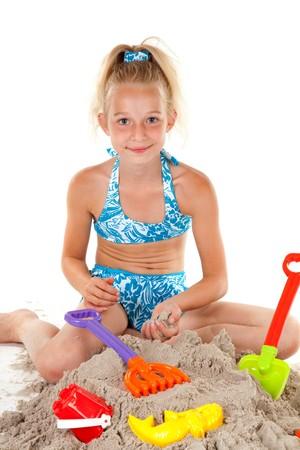 Junge blonde Mädchen im Beachwear spielen mit Sand over white background Standard-Bild - 7361638