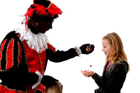 gingernuts: Zwarte piet ( black pete) typical Dutch character part of a traditional event celebrating the birthday of  Sinterklaas in december over white background gives pepernoten ( ginger nuts) to a young girl  Stock Photo