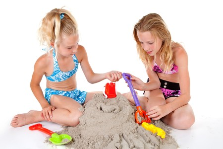 Young blonde girls in beach wear playing with sand over white background Stock Photo - 7361667