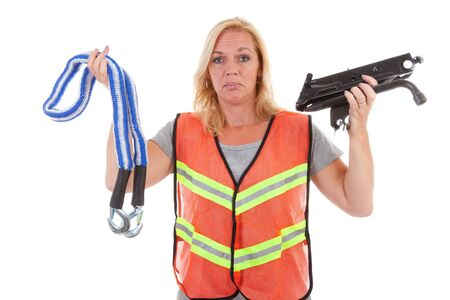 unknowing: Woman in safety vest standing helpless holding car breakdown jack over white background Stock Photo