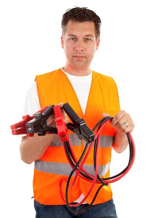roadside assistance: man in safety vest holding car jumper cables over white background Stock Photo