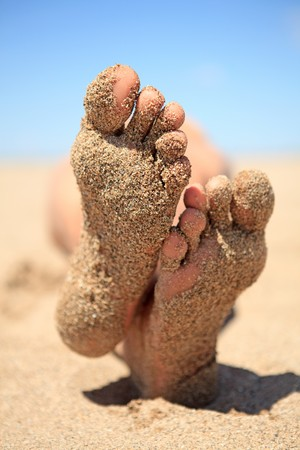 bottom of male feet covered with sand on the beach in sunshine photo