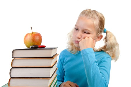 reluctant: Back to school: Young blonde girl is looking reluctant at pile of books over white background Stock Photo