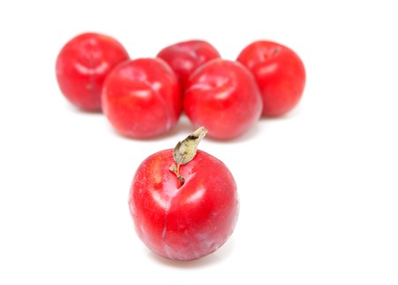 laxatives: couple of red plums with focus on front over white background Stock Photo