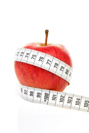 healthy diet; red apple with measure tape over white background Stock Photo