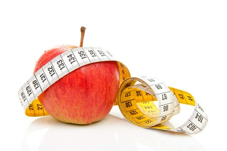 healthy diet; red apple with measure tape over white background photo