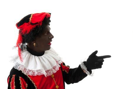 surprised Zwarte piet ( black pete) typical Dutch character part of a traditional event celebrating the birthday of Sinterklaas in december over white background is pointing Stock Photo - 7777401