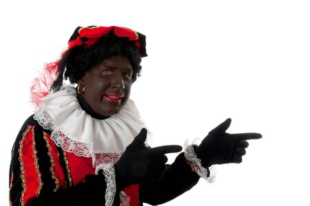 nicolaas: Zwarte piet ( black pete) typical Dutch character part of a traditional event celebrating the birthday of Sinterklaas in december over white background is pointing Stock Photo
