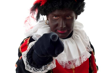 nicolaas: Zwarte piet ( black pete) typical Dutch character part of a traditional event celebrating the birthday of Sinterklaas in december in closeup over white background is pointing at you