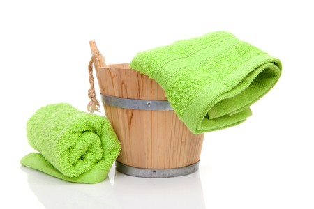 wooden bucket for spa or sauna with green towels over white background