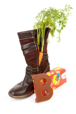 Shoe with carrot, chocolate letter and present over white background, typical Dutch tradition for Sinterklaas in december photo