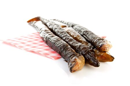 eel: pile of Dutch smoked eel on napkin isolated on white background Stock Photo
