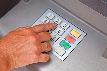 Hand is entering personal identification number on ATM dial panel