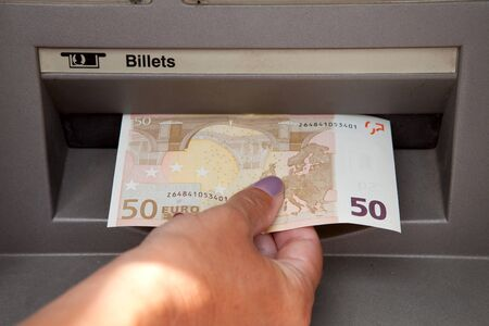 ATM Access : a womans hand withdraws money at cashpoints  photo