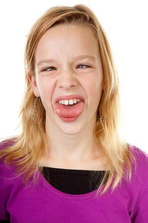 children acting: young girl makes funny face in closeup over white background