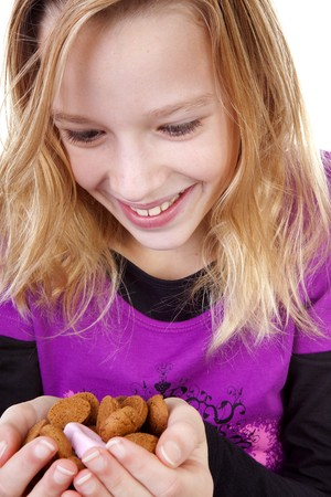 pepernoten: Girl with ginger nuts ( pepernoten ) for Sinterklaas, traditional in the netherlands, over white background