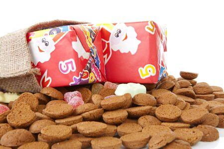 bag with presents and typical dutch sweets: pepernoten (ginger nuts) for a celebration at 5 december in the Netherlands over white background Stock Photo - 8178893