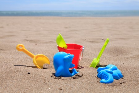 colorful plastic beach toys in the sand near the ocean Stock Photo