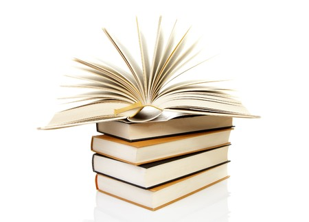 stack of books with open book over white background   photo