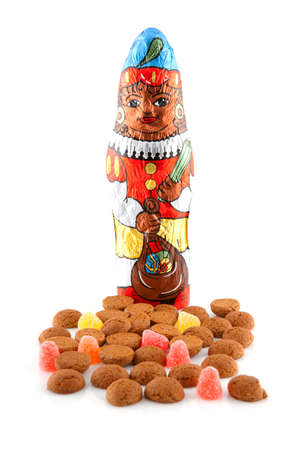 '5 december': Typical dutch sweets: pepernoten (ginger nuts) and chocolate black pete ( zwarte piet) for celebration at 5 december in the Netherlands over white background Stock Photo