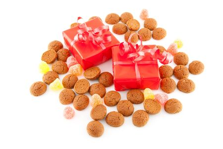 '5 december': Typical dutch sweets: pepernoten (ginger nuts) and red presents for celebration at 5 december in the Netherlands over white background